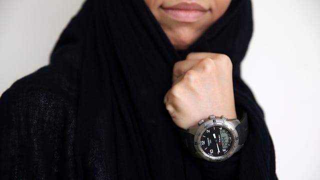 Eine Frau mit schwarzem Schleier zeigt ihre Tissot-Uhr, die sie am linken Handgelenk trägt.