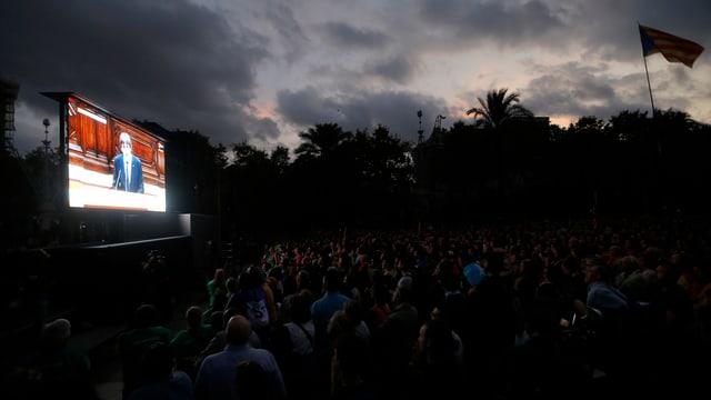 Tausende Menschen schauen unter Palmen auf eine Grossleinwand, auf der Puigdemonts Rede übertragen wird.