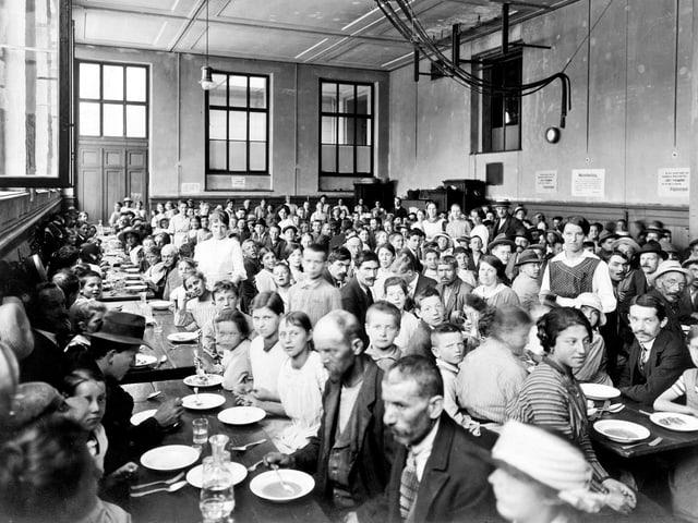 Ein Esslokal in der Dreirosen-Turnhalle. Es ist gefüllt mit Menschen, die essen wollen.