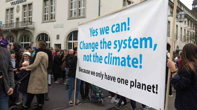 Ein Transparent mit der Aufschrift: Yes we can! Change the system, not the climate!
