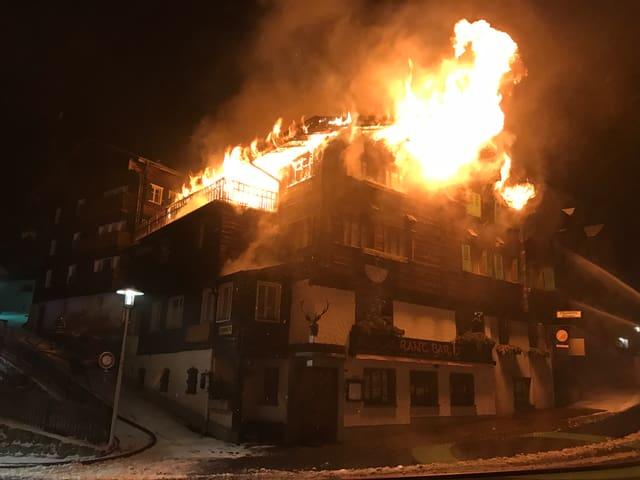 Gebäude in Brand, Flammen dringen aus den Fenstern heraus.