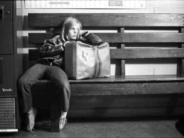 Schwarzweissbild: Ein Mädchen mit gelangweiltem Gesichtsausdruck lehnt sich auf einer Bank gegen einen Koffer.