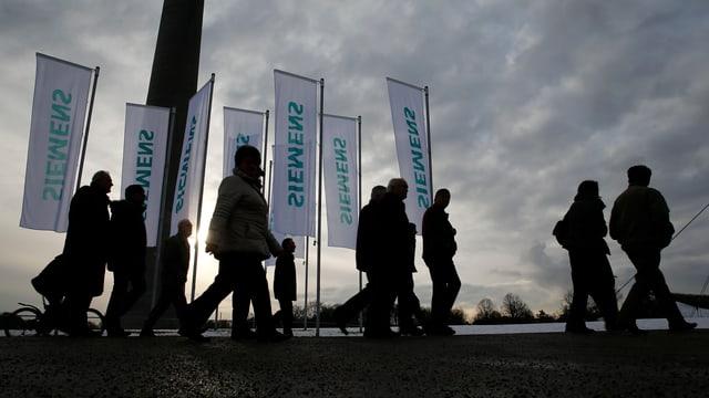 Leute vor Siemensflaggen bei bedecktem Himmel.
