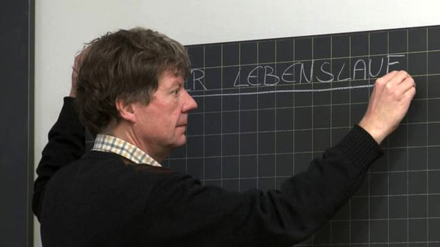 Ein Lehrer schreibt auf die Wandtafel «Der Lebenslauf».