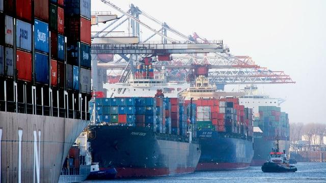 Drei Frachtschiffe hintereinander, alle vollgeladen mit Containern.