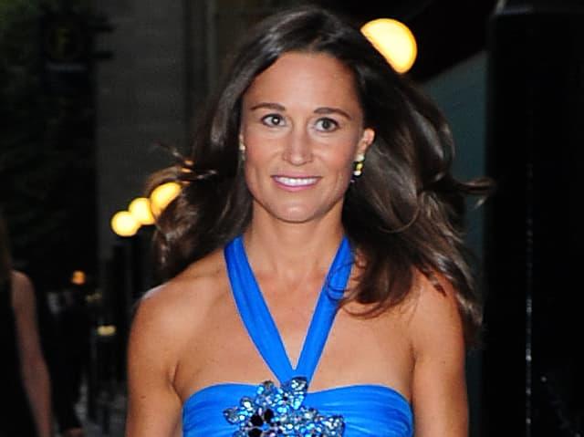 Pippa Middleton mot offenen, wehenden Haaren ud in einem blauen Kleid.
