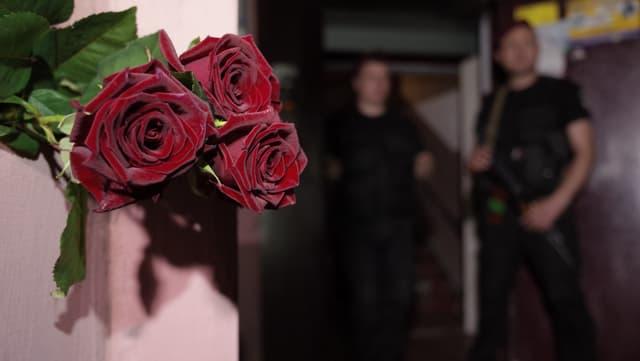 Rosen im Vordergrund, dahinter zwei bewaffnete Sicherheitskräfte.