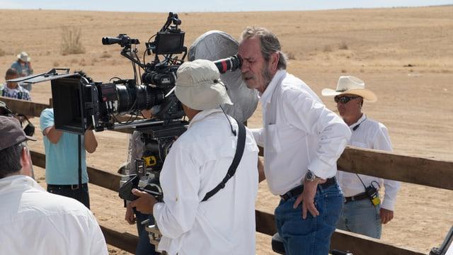 Tommy Lee Jones schaut am Set durch den Sucher einer Filmkamera.