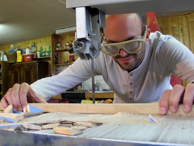 Mann mit Schutzbrille an einer Sägemaschine.