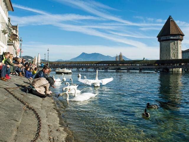 Einheimische und Touristen geniessen das sonnige Herbstwetter an der Reuss in Luzern. (keystone)