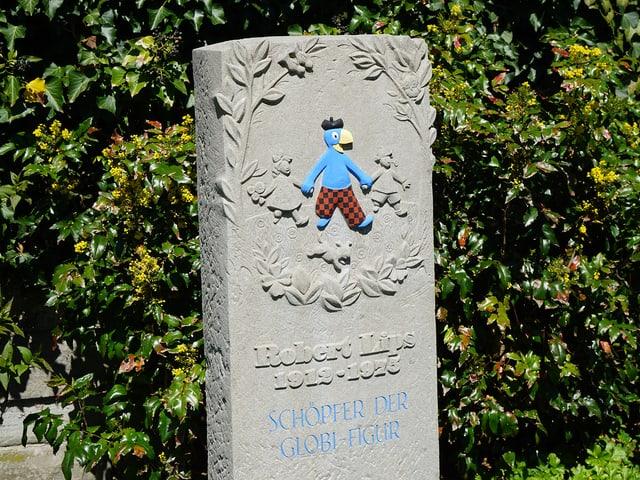 Ein Grabstein, darauf in blau die Globi-Figur
