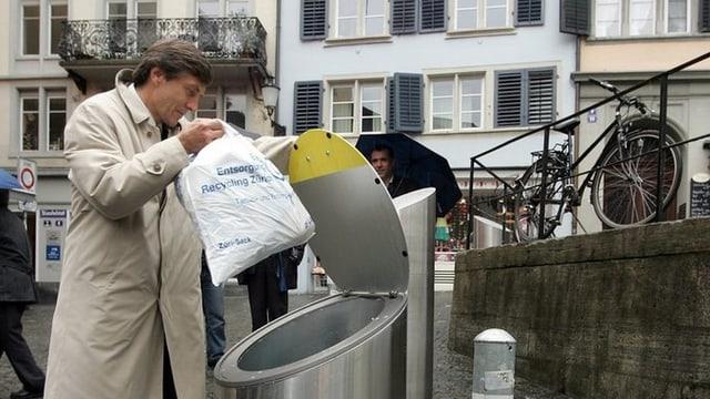 Ein Mann entsorgt einen Kehrichtsack in einem Unterflurcontainer.