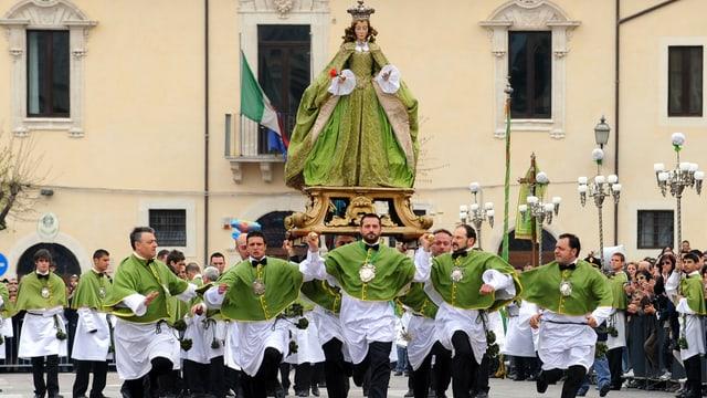 Geistliche tragen eine Madonna-Statue. Sie rennen.