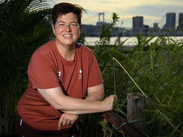 Heidi Diethelm Gerber posiert in Tokio vor dem olympischen Dorf.