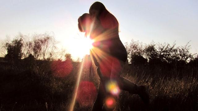 Ein Paar umarmt sich im Sonnenuntergang.