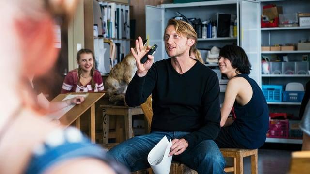 Ein Lehrer sitzt in einem Klassenzimmer und erklärt etwas. Die Schülerinnen und Schüler um ihn herum lachen.