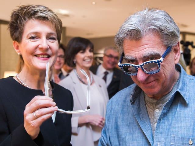 Simonetta Sommaruga hat eine Brille in der Hand und lacht. Daneben steht Nicolas Hayek, der ebenfalls eine Brille hat.