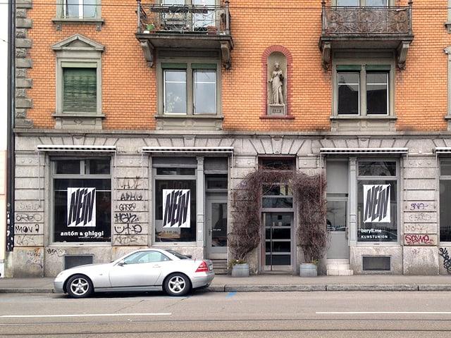 Blick auf drei Schaufenster, in denen je ein Plakat mit der grossen Aufschrift «Nein» hängt.