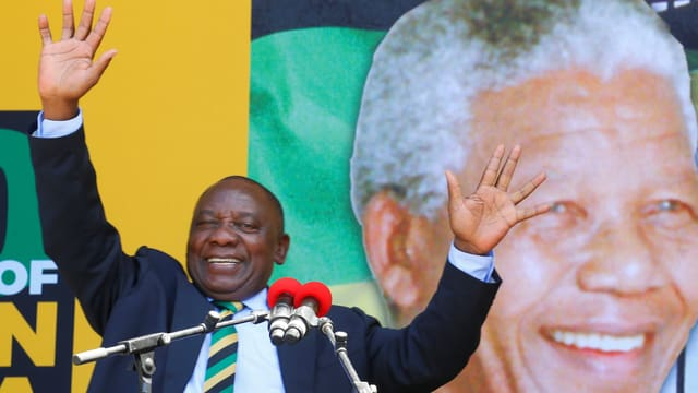 Ramaphosa gestikuliert vor Mikrofonen, hinter ihm eine Grossprojektion von Nelson Mandela.