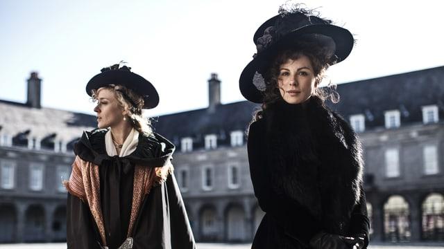 Zwei Frauen stehen mit Umhag und pompösem Hut vor einem symmetrischen Gebäude.