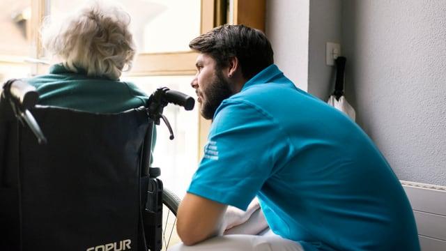 Zivildienstleistender spricht mit betagter Frau in Rollstuhl