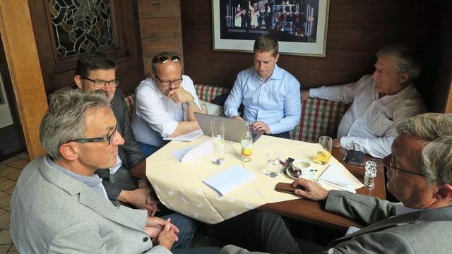Männer sitzen an einem Tisch.