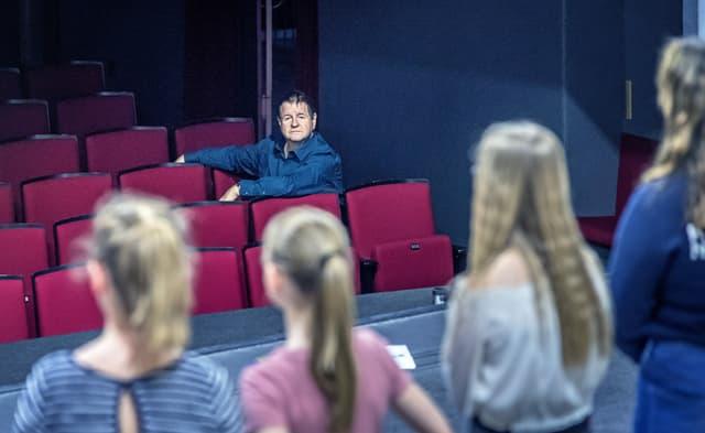 Vier Mädchen stehen auf der Theaterbühne, im Publikum sitzt der Schauspieler und Theatermacher Hanspeter Müller-Drossaart