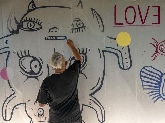 Die Kunstwerke wurden mit schwarzer und grauer Farbe verunstaltet. Künstler Eddie Hara versucht seine Malerei zu retten.