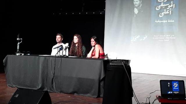 Zwei Frauen und ein Mann sitzen hinter einem Tisch mit Mikrophonen auf einer Bühne.