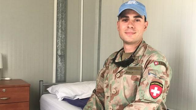 Mann mit blauer Dächlikappe im Kampfanzug und Abzeichen. Er sitzt auf einem Bett.