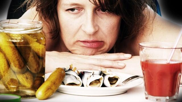 Müpde Frau mustert mit wenig Begeisterung ein Katerfrühstück aus saure Gurken, Rollmops und Tomatensaft.