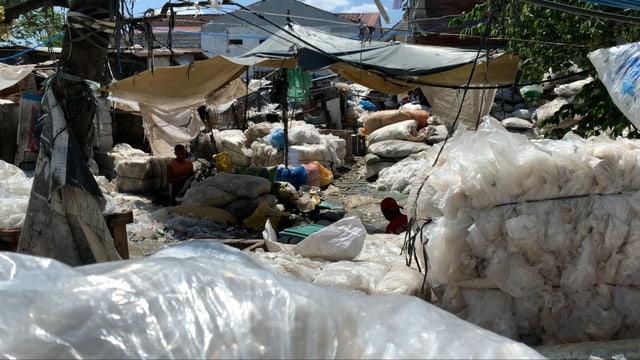Die Umgebung in der NAchbarschaft ist voller Plastik. Im Vordergrund sind saubere Plastikballen im Hintergrund waschen sie Plastik unter einer Plastikplache