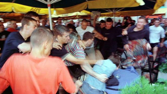 Eine Menschenmenge schlägt auf einen Mann am Boden ein