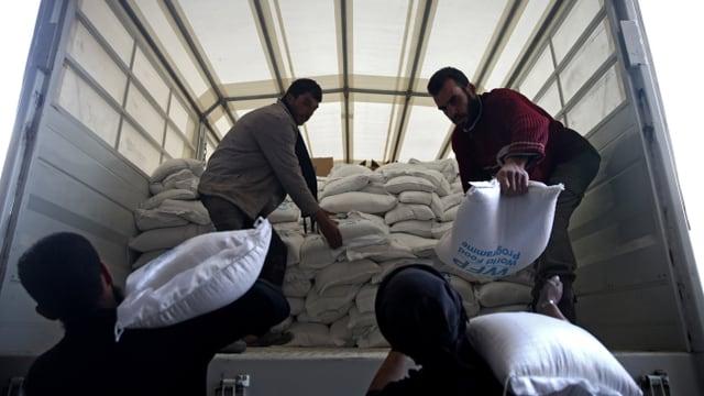 Männer entladen einen Truck mit Hilfsgütern