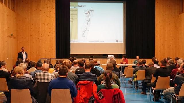 Ein Saal, einige Dutzend Personen sitzen auf Stühlen, vorne steht ein Mann und spricht, auf einer Leinwand ist eine Strassenkarte sichtbar.