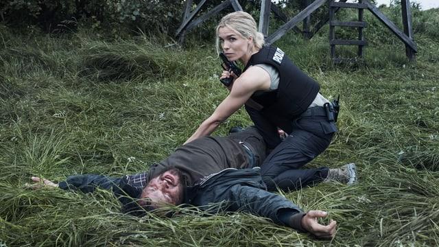 Ein toter liegt auf einer Wiese, eine Polizistin untersucht ihn.