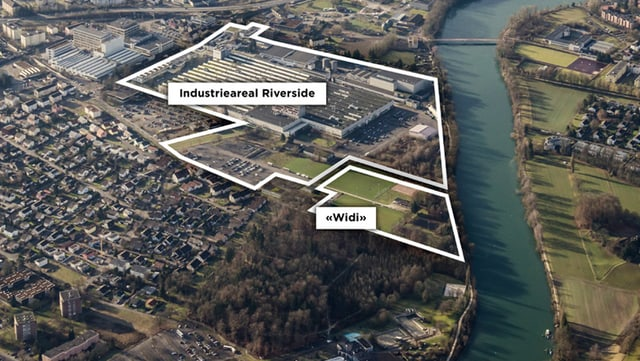 Luftaufnahme eines Industriegeländes mit einem kleinen grünen Landstück neben der Aare (Fluss)