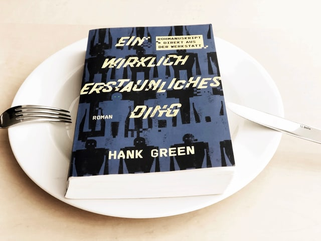Der Roman «Ein wirklich erstaunliches Ding» von Hank Green liegt auf einem weissen Teller