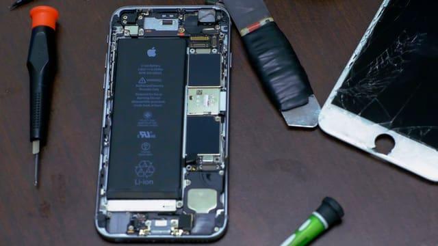 Offenes iPhone, daneben Werkzeug.