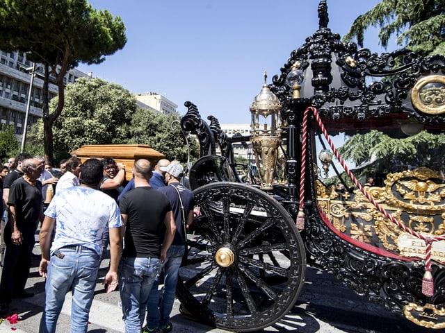 Männer tragen einen Sarg zu einem goldverzierten Leichenwagen.