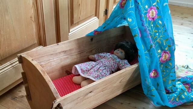 Puppe liegt in einer Holzwiege mit blauem Vorhang.