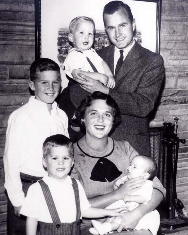 Ein altes Familienporträt. Barbara Bush sitzt auf einem Stuhl und hält ein Baby in ihren Armen. Vater Bush steht hinten und hält Neil im Arm.
