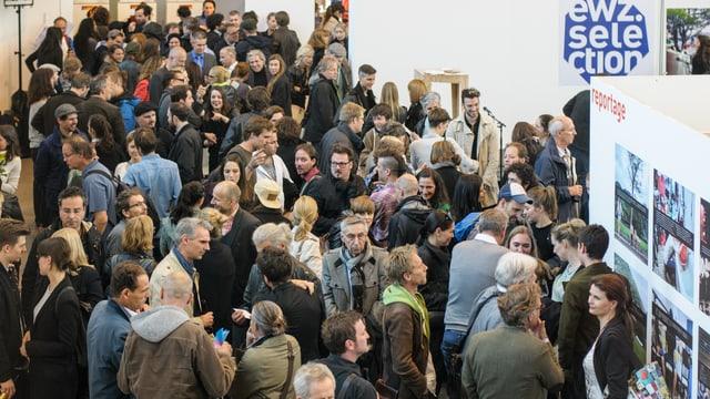Ins vesa bleras persunas a la exposiziun da Fotografias dal premi Swiss Foto Award en la Photobastei a Turich..
