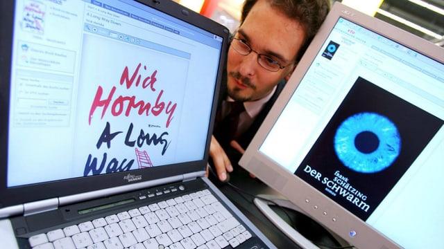 Zwei Computerbildschirme, dazwischen den Kopf eines Mannes.