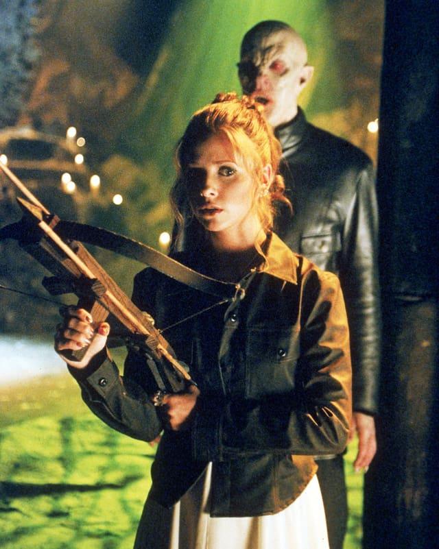 Buffy mit Armbrust, hinter ihr ein Dämon
