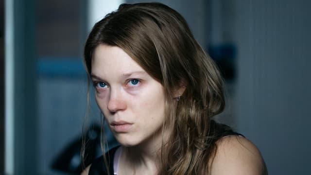 Eine Frau mit blonden Haaren und blutunterlaufenen Augen.