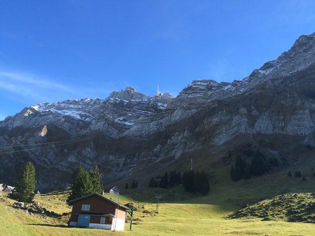Im Vordergrund eine Liftstation, dahinter die Tragseile die zur Bergstion auf den Säntis führen. Am Gipfel ein Sendemast, darüber der blaue Himmel.