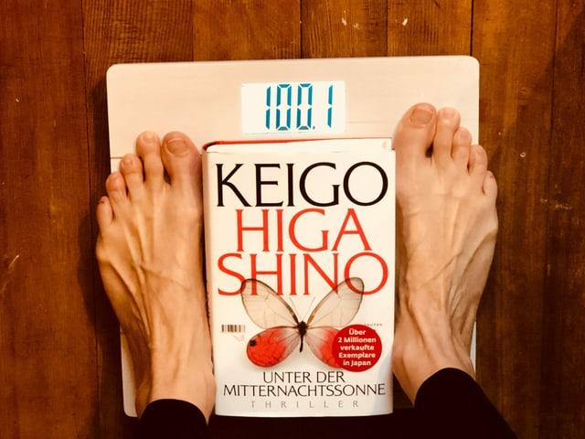 Annette König steht auf einer Waage. Die Anzeige ist 100.1 Kilogramm. Und zwischen den Füssen liegt das Buch «Unter der Mitternachtssonne»