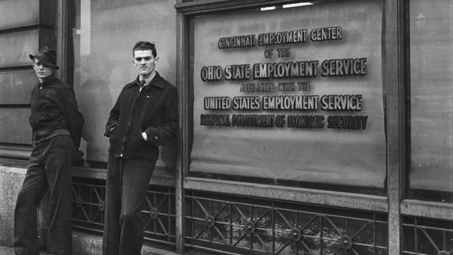 eine schwarz-weiss Fotografie zweier Männer vor einem Gebäude