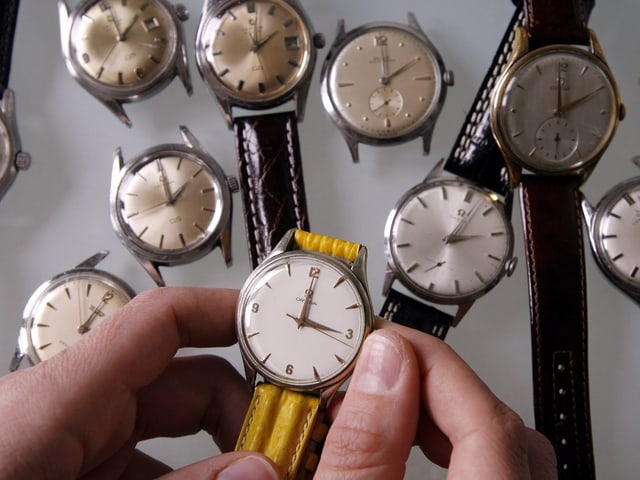 Ein Person stellt eine Uhr.